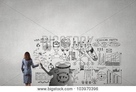 Rear view of young businesswoman drawing strategy plan on screen
