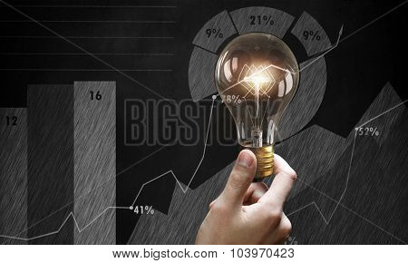 Male hand holding light bulb on background of diagrams and graphs