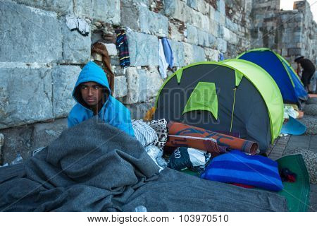 KOS, GREECE - SEP 28, 2015: Unidentified refugee near tents. More than half are migrants from Syria, but there are refugees from other countries -Afghanistan, Pakistan, Iraq, Iran, Mali, Eritrea.