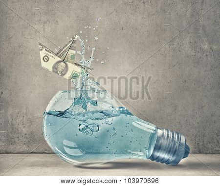 Glass light bulb filled with water and dollar ship floating inside