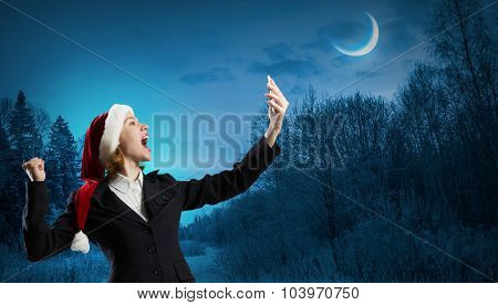Woman in suit and Santa hat screaming in mobile phone