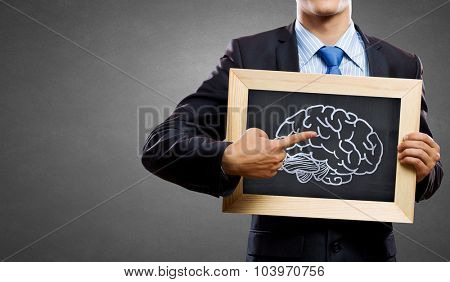 Close up of man holding chalkboard with human mind concept