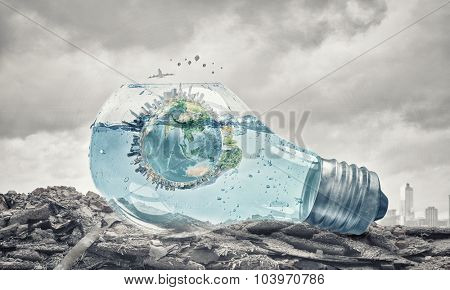Glass light bulb filled with water and floating Earth planet. Elements of this image are furnished by NASA