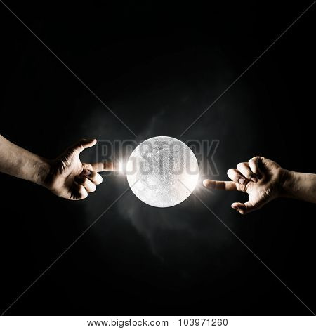 Close up of human hands touching with fingers and moon planet