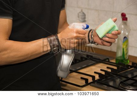Young Man Cleaning Stove Top with Sponge