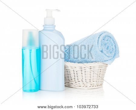 Cosmetics bottles and blue towel. Isolated on white background
