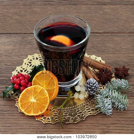 Christmas mulled wine with spices, fruit, holly, mistletoe and winter greenery over oak background.