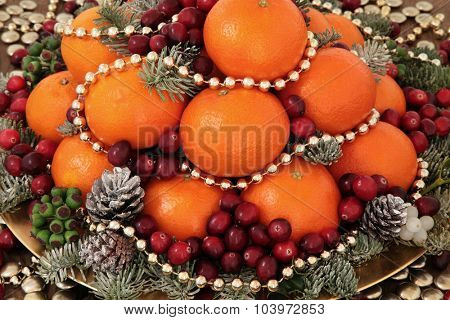 Christmas satsuma orange and cranberry fruit, gold bead decorations, holly, mistletoe and winter greenery over oak background.