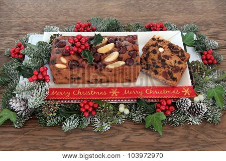 Genoa cake and slices with merry christmas ribbon, holly ,mistletoe and winter greenery over oak background.