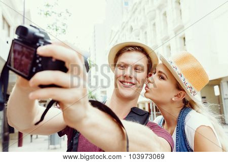 Happy young couple as tourists with a camera