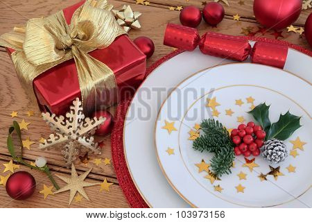 Christmas holiday dinner place setting with plates, gift box, bauble decorations, holly and mistletoe over oak table  background.