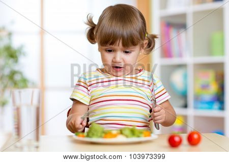 Unhappy child sitting at breakfast and uncertainty looking at food