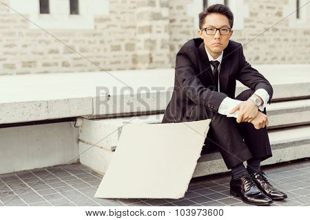 Businessman in a city street hsitting next to blank banner