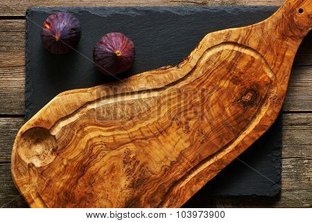 Olive wood cutting board and figs over slate