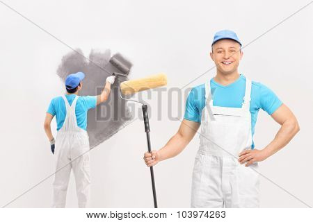 Young male painter looking at the camera and other painter painting a wall with gray color in the background