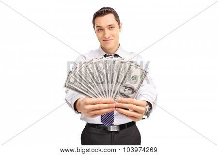 Confident young businessman holding a stack of money and looking at the camera isolated on white background