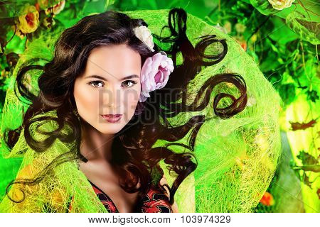 Happy beautiful brunette woman among summer plants and flowers. Beauty, fashion. Spa, healthcare. Tropical vacation.
