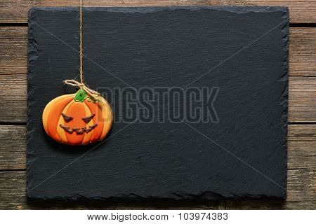 Halloween homemade gingerbread cookie over slate background