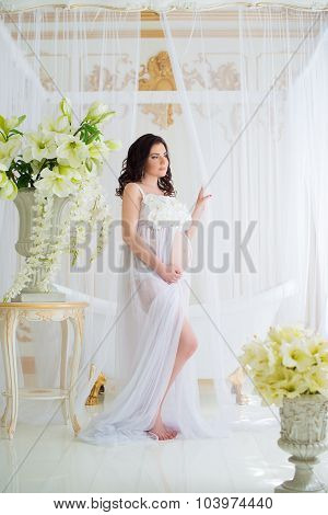 Beautiful Pregnant Girl In Interior With Flowers And Tulle Curtains