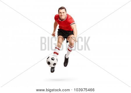 Young sportsman kicking a football in mid-air and looking at the camera isolated on white background