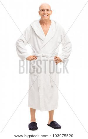 Full length portrait of a relaxed senior man in a white bathrobe smiling and looking at the camera isolated on white background