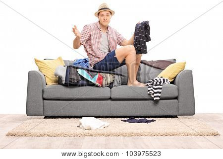 Sad young man sitting on his overstuffed suitcase and gesturing with his hands isolated on white background