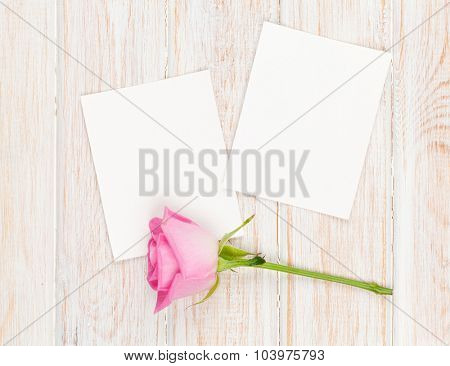 Two blank photo frames and pink rose over wooden table