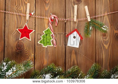 Snow fir tree and christmas decor on rope over rustic wooden board with copy space