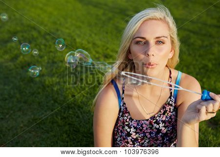 Attractive blonde woman blowing soap bubbles in park summer fun outdoors