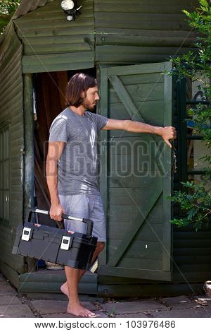 male technician handyman carrying toolbox closing his garden toolshed