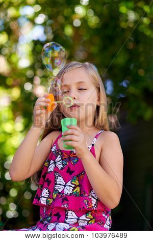 Cute little caucasian girl blowing soap bubbles, innocent blissful childhood