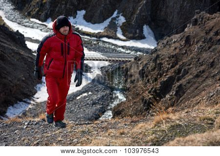 Man in wilderness rugged mountain landscape determined to climb to the summit in red snow gear