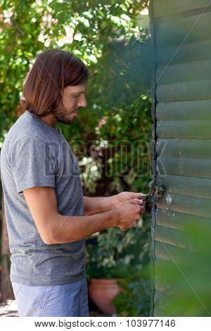 young caucasian male locks door of his garden diy workshop