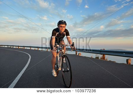 Young caucasian woman riding a bike on the road