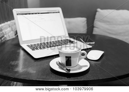 Black And Whte Scene Of Laptop With Tablet, Pen And A Cup Of Fresh Coffee Latte Art On Wooden Table