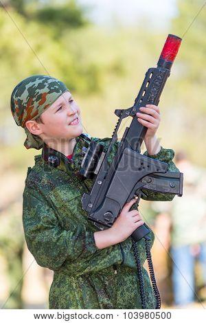 Boy with a gun playing lazer tag open air