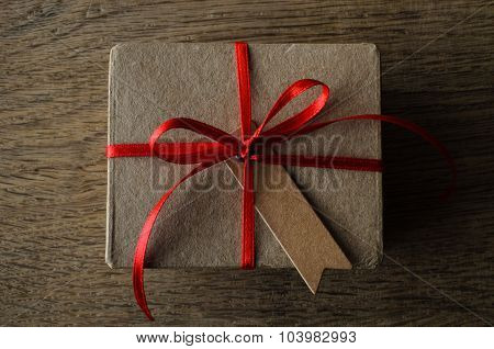 Plain Gift Box Overhead On Oak Wood With Vintage Style Label And Red Ribbon