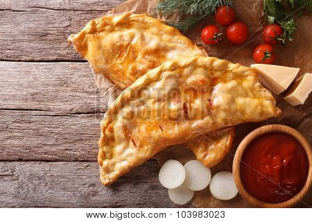 Pizza Calzone On A Paper And Ingredients. Horizontal Top View
