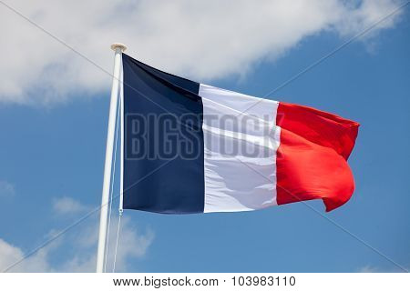 French Flag Against Blue Cloudy Sky