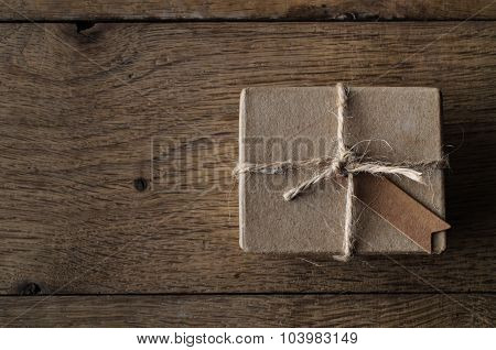 Simple String Tied Box With Vintage Style Tag On Old Oak Wood Table