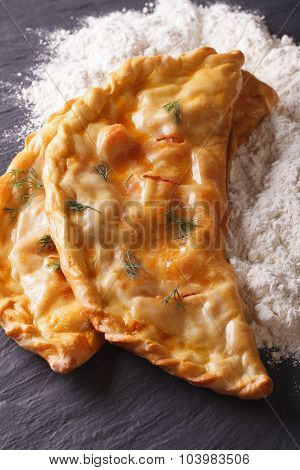 Italian Pizza Calzone And White Flour Close-up. Vertical Top View