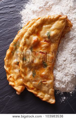 Italian Food: Pizza Calzone And Flour Close-up. Vertical Top View