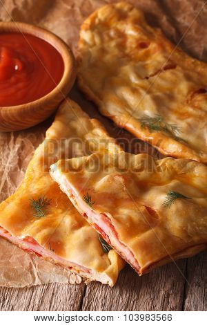 Cut Italian Pizza Calzone With Ham And Cheese Close-up. Vertical