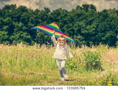 little cute girl flying a striped kite in a meadow on a sunny day