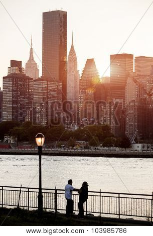 Two people enjoy the view across the East River of the New York skyline