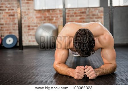 Shirtless man doing push ups at the gym