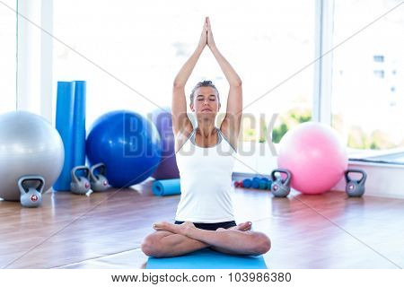 Woman doing lotus poster with arms overhead in fitness studio