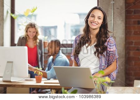 Portrait of businesswoman using laptop while colleague seen in background at creative office