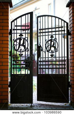 Black wrought iron and brick entrance gates
