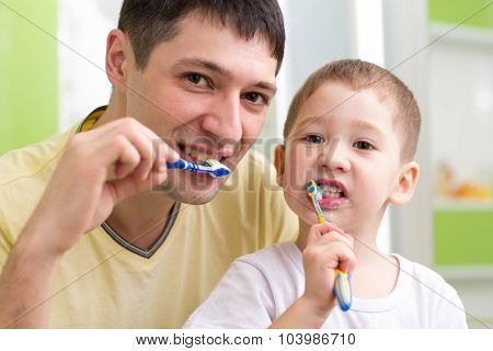 child and his father brushing teeth in bathroom